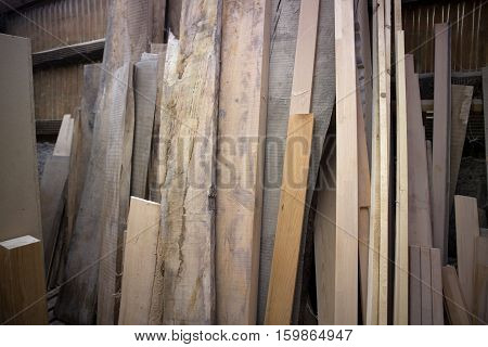 wooden planks leaning against a wall at a workshop