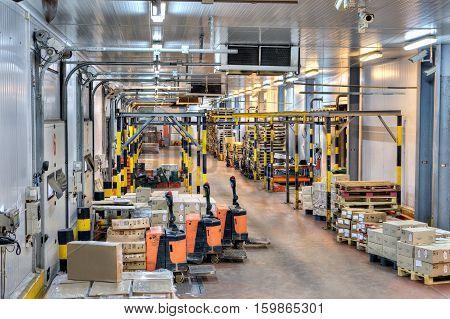 Saint-Petersburg Russia - October 31 2016: warehouse loading dock interior and electric powered pedestrian pallet trucks.