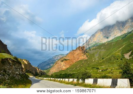 Mountain road passing between the rocks and flowering meadows