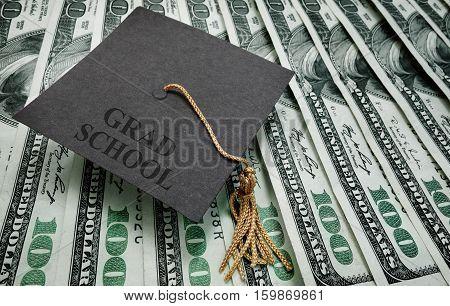 graduation cap with Grad School text on hundred dollar bills
