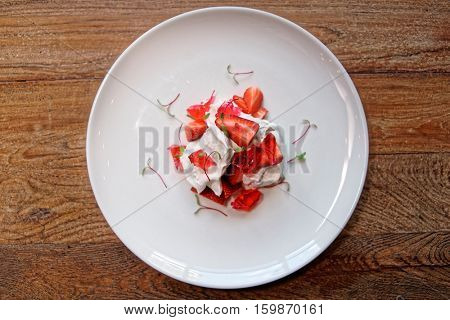 Meringue dessert with ripe strawberries and jam on wooden table