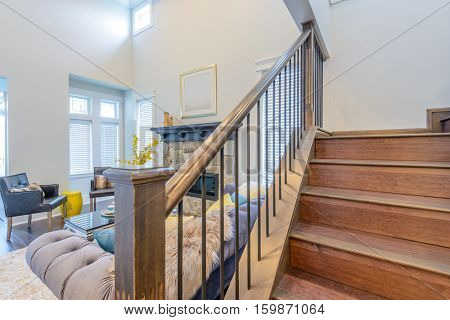 Beautiful living room interior with hardwood floors and vaulted ceiling in new luxury home. View of stairs, and second story loft style area.