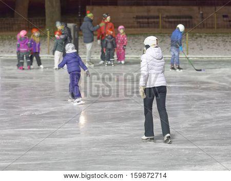 STOCKHOLM SWEDEN - DEC 03 2016: Children and adults skating in the park during the night. Vasaparken Stockholm Sweden