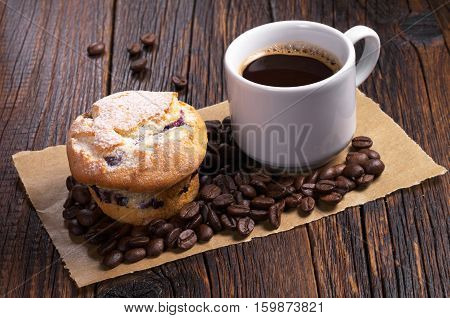 Cup of hot coffee and muffin on dark wooden table
