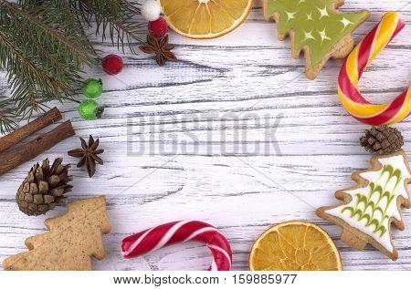 Christmas Xmas New Year holiday Background with dried oranges cookies star anise cinnamon cones natural fir branches cande cane on white wooden table