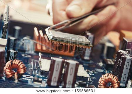 Engineer plug in CPU microprocessor to motherboard socket
