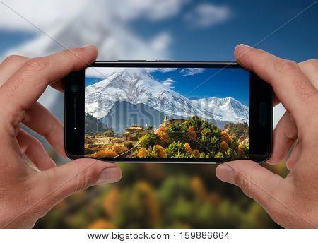 Travel concept. Tourist making photo of Himalayas mountain landscape. Buddhist monastery and Manaslu mount in Himalayas, Nepal.