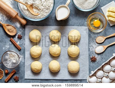 Buns dough preparing recipe bread or pie making ingridients, food flat lay on kitchen table background. Working with butter, milk, yeast, flour, eggs, sugar pastry or bakery cooking.