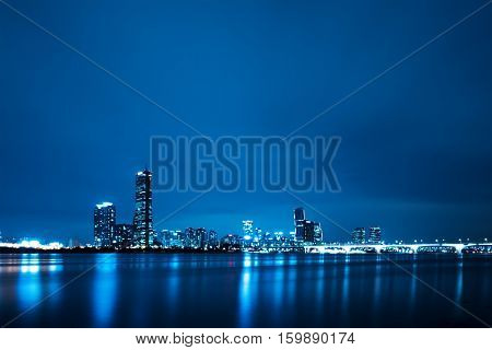 modern office buildings  near bridge  from river in seoul at night