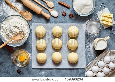 Buns dough traditional homemade preparing recipe, ingridients food flat lay on kitchen table background. Working with butter, milk, yeast, flour, eggs, sugar pastry or bakery cooking.