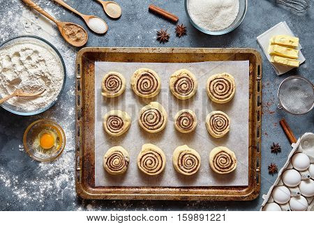 Cinnamon rolls or cinnabon handmade raw dough preparation sweet traditional dessert buns pastry food baked homemade swirl Danish mini snack. Food ingridients flat lay on kitchen table. Top view