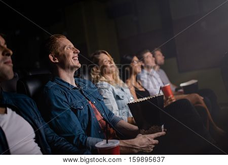 Group of people sitting in multiplex movie theater and watching movie. Happy young friends watching movie in cinema.