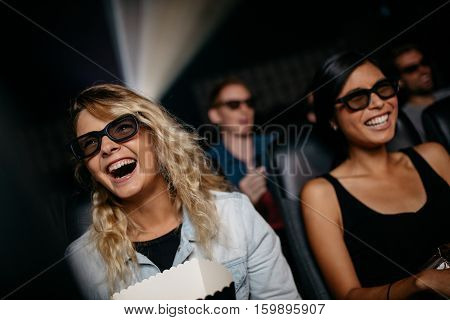Female friends watching 3d movie and laughing in cinema. Happy young women watching 3d film in theater.