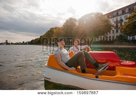 Shot of two young friends sitting in pedal boat and pedaling. Teenage boys boating on the lake in city.