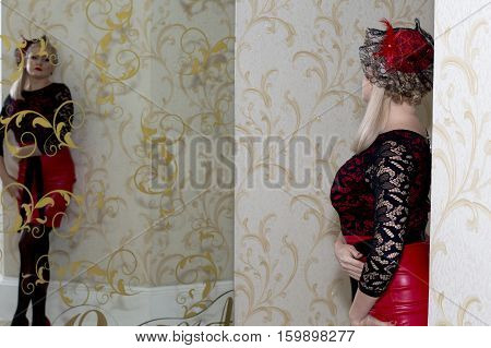 the bright blonde in a red dress looks at the reflection a subject holidays and beautiful women