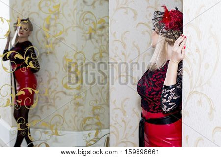 the bright blonde in a festive dress looks at the reflection a subject holidays and beautiful women
