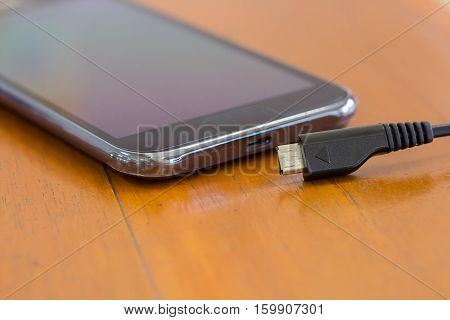 Close up of smart phone charging with USB cable on wooden texture background