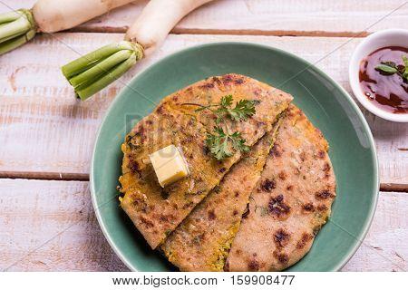 Daikon, radish, mooli or muli paratha or stuffed radish paratha, indian or pakistani favourite recipe served with butter and tomato ketchup, selective focus