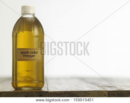 Bottle of clear filtered Apple Cider Vinegar on white background.