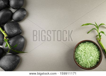 Spa stones with bamboo branch and sea salt on color background