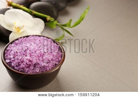 Spa stones, sea salt and orchid flower on color background
