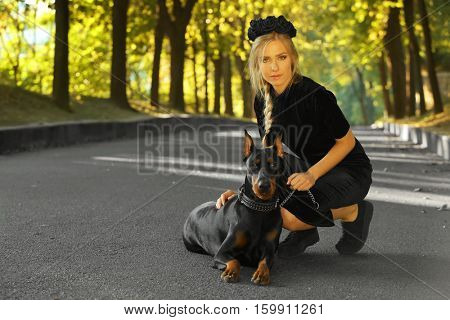 Beautiful young woman in park with her dog