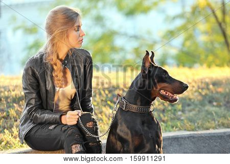 Beautiful young woman and her dog in green park