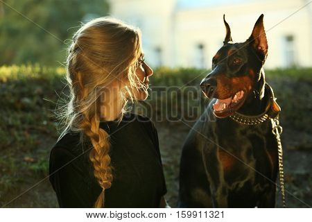 Portrait of beautiful young woman with her dog on blurred background