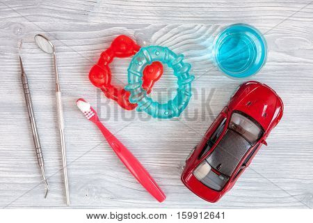 children's toothbrush oral care on wooden background top view.