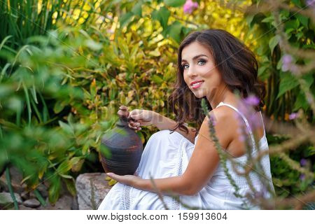 Lovely girl in a white dress holding a little old pitcher.