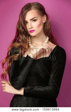 Portrait of gorgeous young woman in black evening gown on pink background