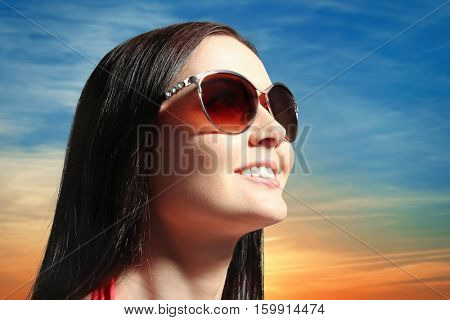 Young woman in sunglasses on sky background