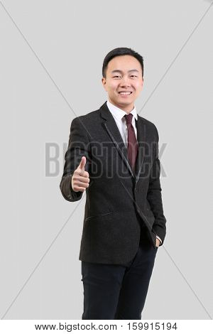 Handsome Asian man showing thumb up sign, on light background