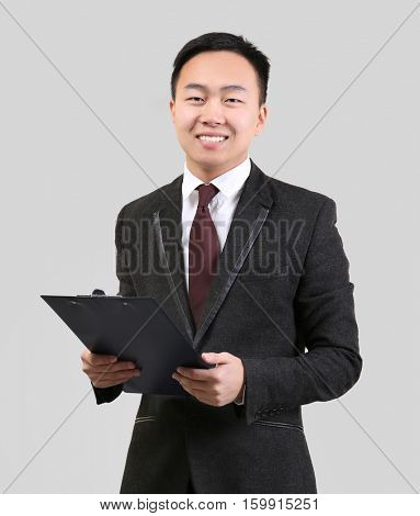 Handsome Asian man with clipboard on light background