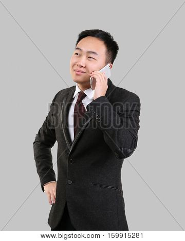 Handsome Asian man talking by mobile phone, on light background
