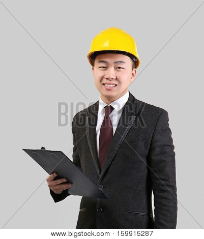 Handsome Asian man with clipboard and hardhat on light background