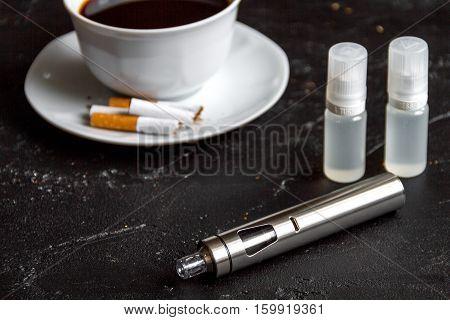 elimination of tobacco smoking electronic cigarette on dark background close up