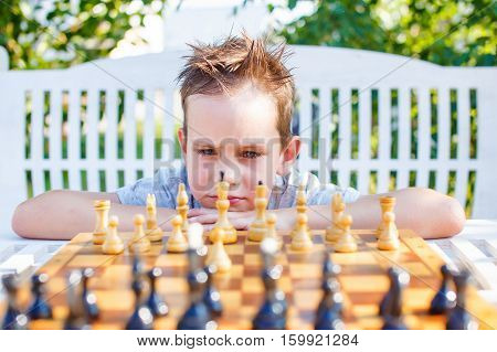 stressful child at the chessboard. boy thinking hard on chess combinations. playing chess outdoors. selective focus