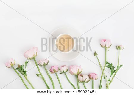 Beautiful spring Ranunculus flowers and cup of coffee on white table from above. Greeting card. Breakfast. Pastel color. Clean space for text. Flat lay style.