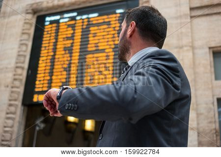 Businessman checking time while watching at a time table monitor