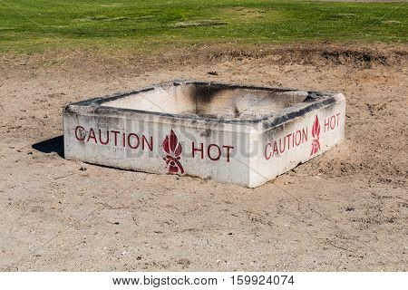 Fire pit on beach with grass in background.