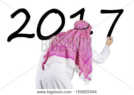 Image of Arabian businessman wearing headscarf and writing numbers 2017 with marker on the whiteboard in the studio