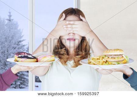 Portrait of beautiful woman refusing junk food with winter background on the window