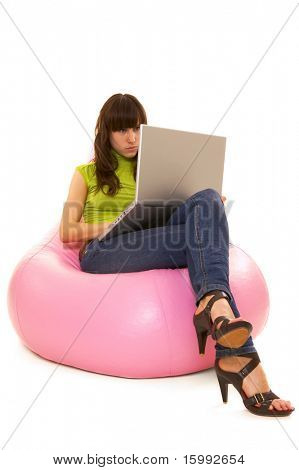 concentrated woman with laptop sitting on pink chair