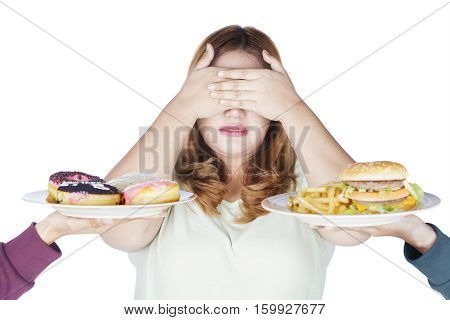 Portrait of fat woman close her eyes by using hands and reject junk food isolated on white background