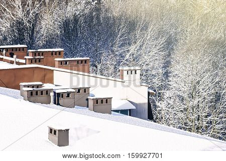 Winter view from above. Apartment building roof and trees covered by snow