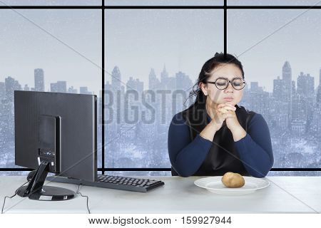 Portrait of fat woman praying in front of potato on plate with winter background on the window
