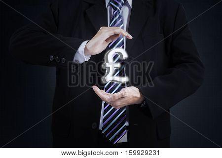 Businessperson hands holding a pound currency sign and wearing formal suit