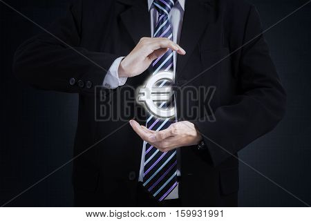 Image of businessperson hands holding Euro currency sign while wearing formal suit