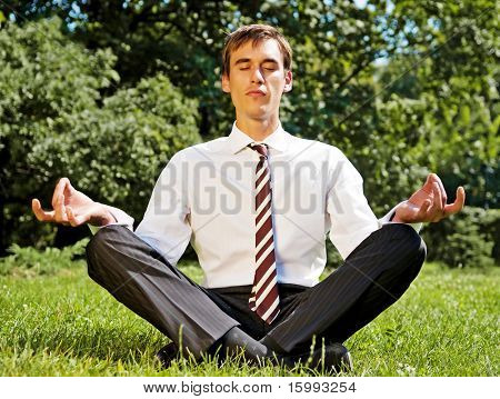 young businessman meditating on the grassland